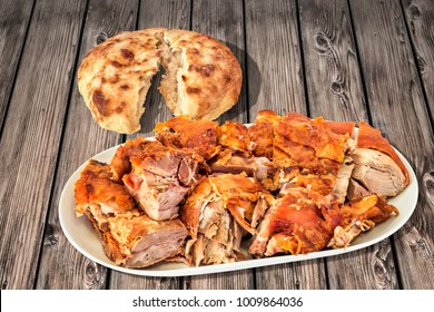 Plateful Of Freshly Spit Roasted Pork Shoulder Slices And Leavened Pitta Flatbread Torn Loaf Set On Old Weathered Cracked Pinewood Garden Table
