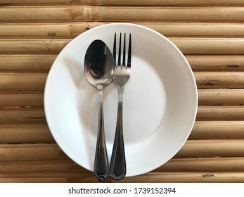 Plates and cutlery on bamboo table.