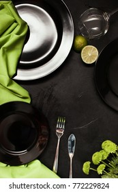 Plates and cutlery on black background with contrast green color. Exquisite restaurant table setting. Art and design concept