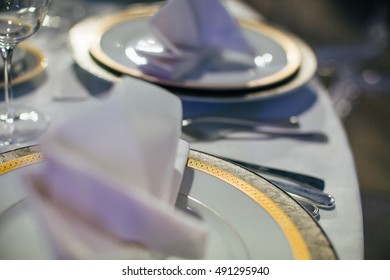 Plates with grey and golden ornament stand on the white table