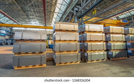 Plates of metal coils stacked in an industrial warehouse.