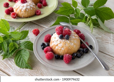 plates of muffins with fresh berries on a light wooden table