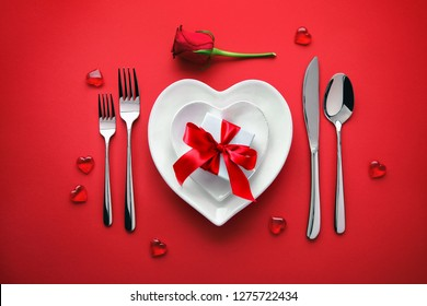 Plates in shape of heart, holidays table setting with a gift box on red background