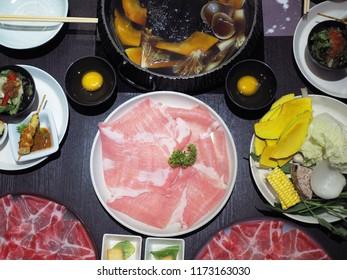 Plates of thin sliced pork meat (pork neck or pork blade shoulder) prepared for shabu or sukiyaki or Japanese hot pot. Selective focus.