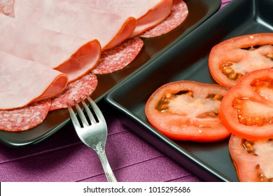 Plates with tomatoes, ham, sausages on the table
