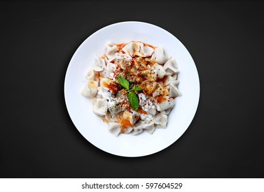 Plates of traditional Turkish food. Manti with tomato sauce.