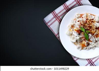 Plates of traditional Turkish food. Manti(Turkish ravioli) with tomato sauce.