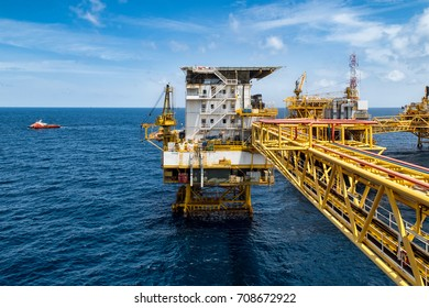 Platform Offshore oil and Gas processing platform for oil and gas industry, gases sent to onshore refinery, petrochemical and power generation plant with transportation boat. Industry concept.