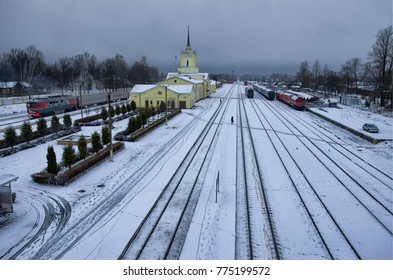 """Platform and station Dno in the winter evening. The name of the station is written on the building by red paint in Russian """"Dno"""". Pskov Oblast, Russia"""