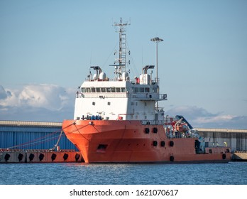 Platform supply vessel anchored in sea port at sunny day. Front view of offshore support vessel