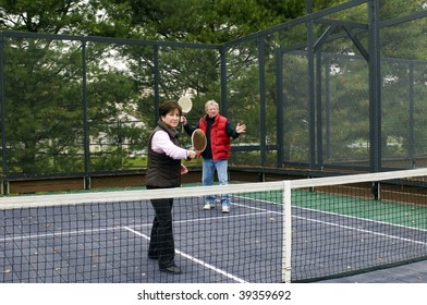 platform tennis game played by middle age retired senior man and woman on suburban paddle court