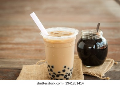 Platic cup of Taiwan iced milk tea with bubble boba fresh drink in the sun shine day put with bubble in glass cup on the wood floor