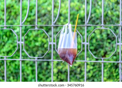 Platic garbage, plastic bag used for sparkling water was left on fence in city.