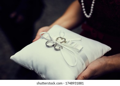Platinum wedding rings fastened with ribbons on a white cushion, held by a woman in her hands