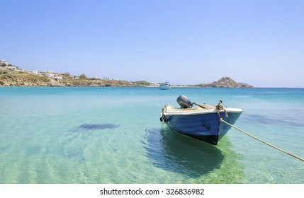 Platis Gialos beach on greek island Mykonos, Greece. A view of the crystal clear blue sea and a boat tied in the water on a summer day.