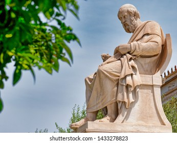 Plato the ancient Greek philosopher white marble statue and orange tree foliage on sky background, Athens Greece