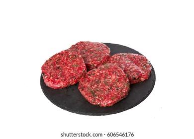 Plato negro con cuatro hamburguesas crudas de perejil sobre fondo blanco