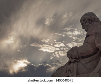 Plato statue, the ancient Greek philosopher, under impressive cloudy sky with sun patches