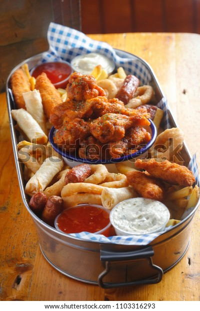 Platter with chicken goujons, crispy chicken wings, cocktail sausages, veg spring rolls, onion rings & fries served with dips