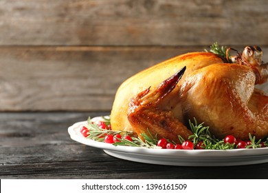 Platter of cooked turkey with garnish on wooden table. Space for text