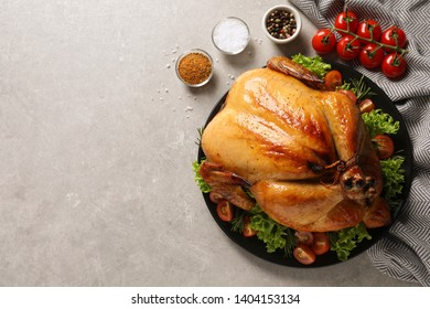 Platter of cooked turkey with garnish and spices on grey background, flat lay. Space for text