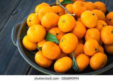 A platter of fresh orange Clementine tangerines on dark wooden background close-up