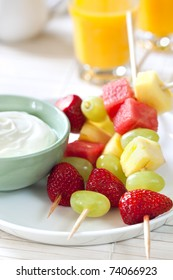 Platter of fruit skewers with a dish of yogurt.  Healthy party food, with orange juice behind.