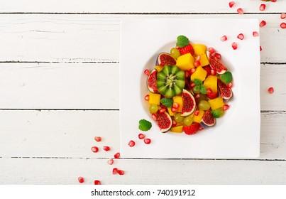 Platter fruits and berries. Mango, kiwi, fig, strawberry, grapes, pear and orange. Vegan cuisine. Dietary menu. Flat lay. Top view