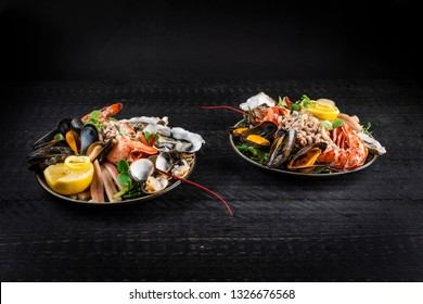 Platter with fruits de mer, seafood, lobster, clams, mussels, oysters, shrimps, black background