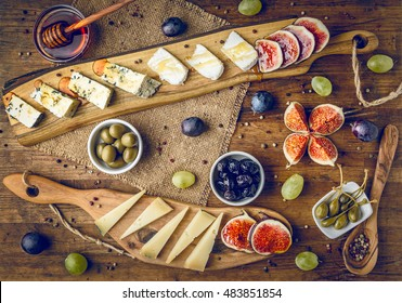 platter of italian cheeses with figs, olives, grapes and honey toned