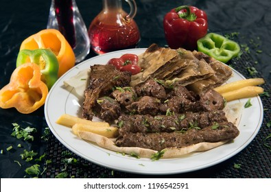 A Platter of mixed grilled food (Meat, beef Arayes, Fries and Kabab) Arabic meal ready for lunch or dinner at restaurant with fresh health capsicum and sauce