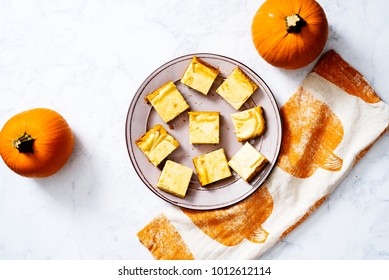 Platter of pumpkin cheesecake bars on a gray plate on white marble surface with whole pumpkins and a pumpkin linen.