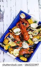 Platter of seafood with lobster, clams, potatoes and corn.