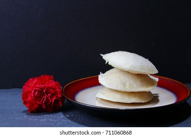 A platter of a south Indian Idli or rice and lentils steamed cakes with a spicy soup and coconut chutney