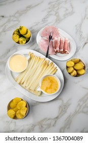Platter white German asparagus with potatoes, cooked and smoked ham, Sauce Hollandaise and melted butter on marble background