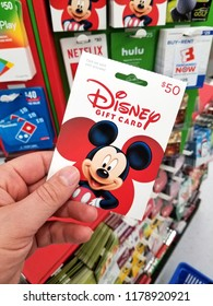PLATTSBURGH, USA - SEPTEMBER 10, 2018: A man holding Disney gift card. Walt Disney or simply Disney, is an American diversified multinational mass media and entertainment conglomerate
