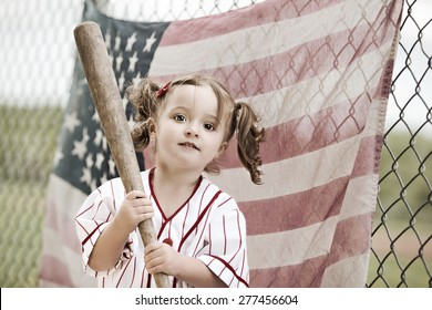 Play Ball!  Adorable toddler wearing a vintage baseball uniform and holding a baseball bat.  A faded American flag hanging from a chain link fence in the background.