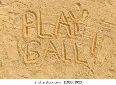 Play ball written in sand on baseball diamond