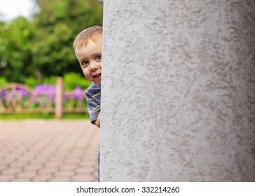 play bo-peep. child playing hide and seek outdoors peeking from behind a pillar