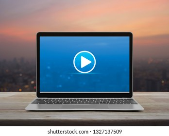 Play button with modern laptop computer on wooden table over blur of cityscape on warm light sundown, Business music online concept