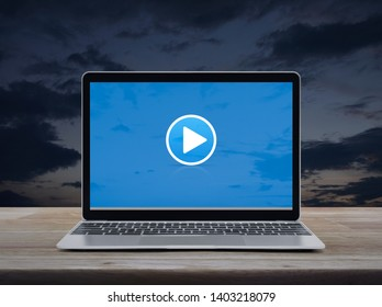 Play button with modern laptop computer on wooden table over sunset sky, Business music online concept