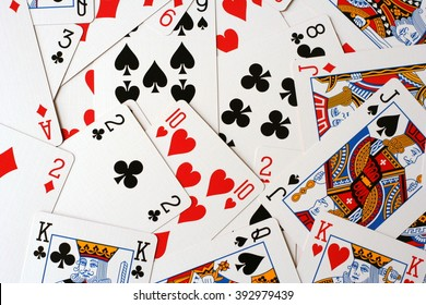 Play cards scattered on the table. Cards deck scattered. Play cards different colors. Play cards for bridge or poker (king, jack, queen...). Disarranged cards collection.