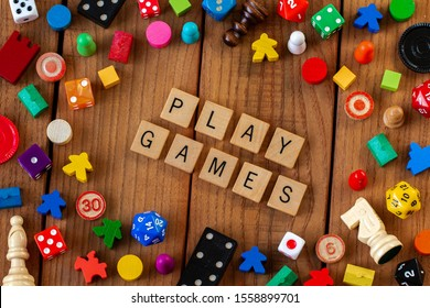 """Play Games"" spelled out in wooden letter tiles. Surrounded by dice, cards, and other game pieces on a wooden background"