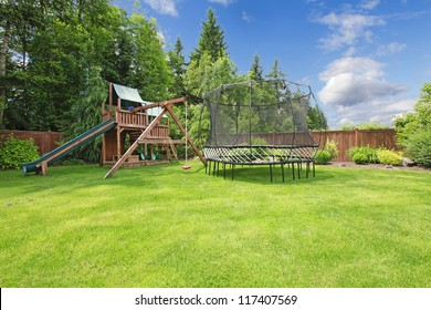 Play kinds ground area with trampling in fenced backyard during summer.