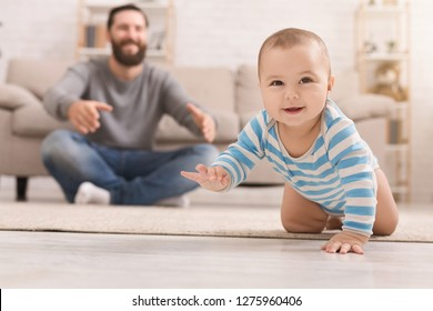 Play with me. Adorable baby boy crawling on floor at home, daddy watching his son, copy space
