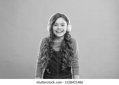 Play the moment. Cute kid listening to music in stereo headset. Adorable headset user on blue background. Small child wearing adjustable white headset. Little girl using wireless headset.