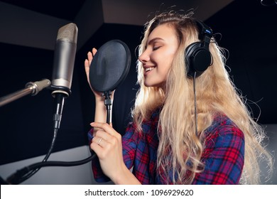 Play on! Gorgeous good-looking female vocal artist singing in the modern recording studio in order to create new album.