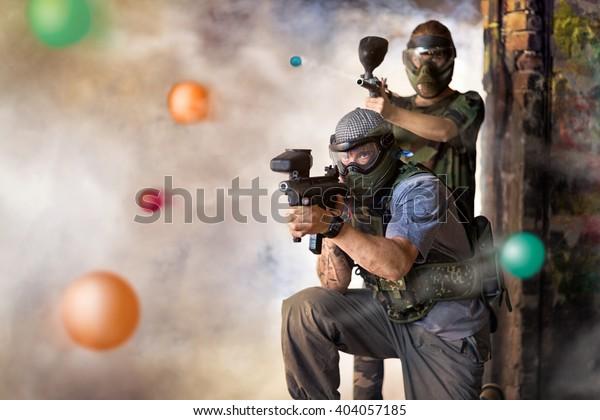 Hrát paintball, dva hráči se zbraněmi