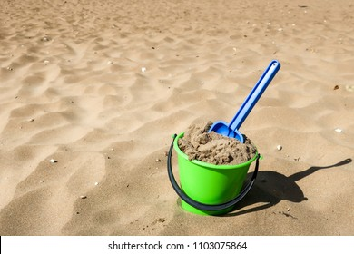 Play in sand.  Green plastic bucket and blue shovel on a beach. Concept for traveling with children / family vacation and holiday. Copy space.