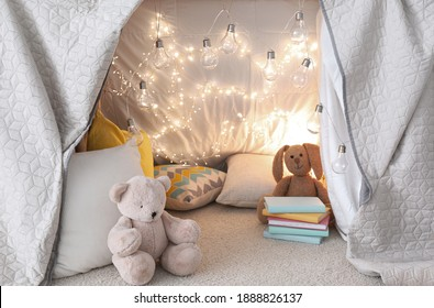 Play tent with toys and pillows indoors, closeup. Modern children's room interior